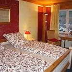 Großes rotes Schlafzimmer mit einem Doppelbett und einer Sitzgruppe am Abend mit Nachtlich in der Panorama Pension Ahrklause Dernau.
