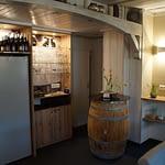 Holzbar mit Kühlschrank, Weinflaschen, Gläsern sowie einem Holzfass welches als Stehtisch umgebaut wurde in dem Frühstücks- und Aufenthaltsraum der Panorama Pension Ahrklause Dernau.