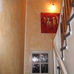 Treppenhaus mit blauem Teppich und weißem Holzgeländer des Ferienhaus Tant Anna Dernau an der Wand hängt ein rotes Gemälde.