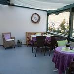 Terasse mit Rattanstühle einem Tisch mit Lila Tischdecke und grünem Tischläufer, der Panorama Pension Ahrklause Dernau.