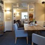 Weißer Holzdurchgang im Frühstücks- und Aufenthaltsraum der Panorama Pension Ahrklause Dernau mit einem großen Holztisch mit Lounge Stühlen und roten Tulpen auf einem Holzfass stehend.