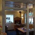 Weißer Holzdurchgang im Frühstücks- und Aufenthaltsraum der Panorama Pension Ahrklause Dernau mit einem alten Holzschrank sowie Holztischen und Holzstühlen roten Tulpen auf einem Holzfass stehend.
