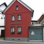 Das Ferienhaus Tant Anna Dernau mit roten Außenwänden und einer grün weiß gestreiften Hoftürevon der Straßenansicht.