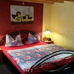 Rotes Schlafzimmer des Ferienhaus Tant Anna Dernau mit einem Bett und einem Bild mit Engeln darauf.