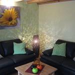 Wohnzimmer des Ferienhaus Tant Anna Dernau mit einem Braunen Sofa einem Holztisch und einem Gemälde mit einer gelben Blume darauf.