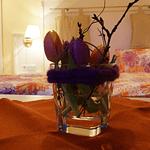 Blumenschmuck auf einem Tisch im Hintergrund ein Bett bei gedämpftem Licht in der Panorama Pension Ahrklause Dernau.