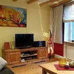 Wohnzimmer des Ferienhaus Tant Anna mit Holzboden einem Lowboard aus altem Holz einem Fernseher, einer Stereoanlage und einem bunten Gemälde an der Wand.