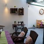 Terasse mit einer alten Nähmaschiene, einem alten Ofen, Rattanstühle einem Tisch mit Lila Tischdecke und grünem Tischläufer, der Panorama Pension Ahrklause Dernau.