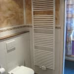 Badezimmer des Ferienhauses Tant Anna Dernau mit einer Toilette und einer Heizung.