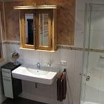 Badezimmer des Ferienhauses Tant Anna Dernau mit einer Dusche und einem Waschbecken über dem ein Schrank aus einem alten Holzfenster hängt.
