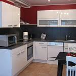 Weiße Küche des Ferienhaus Tant Anna Dernau mit einer schiefergrauen Arbeitsplatte und einer roten Wand.