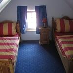 Zweites Schlafzimmer unter dem Dach mit zwei einzelnen Holzbetten blauem Teppich des Ferienhaus Tant Anna Dernau.