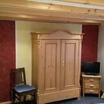Schlafzimmer des Ferienhaus Tant Anna Dernau mit einem Alten Holzschrank und einem Fernseher.