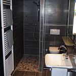 Großes modernes Badezimmer mit dunklen Fließen und weißer Decke mit einer begehbarer Dusche einer Toilette und einem Waschbecken der Panorama Pension Ahrklause Dernau.