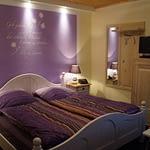 Großes lila Schlafzimmer mit einem Doppelbett und einem Schrank mit Fernseher am Abend mit Nachtlich in der Panorama Pension Ahrklause Dernau.