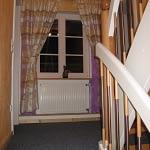 Treppenhaus mit blauem Teppich und weißem Holzgeländer des Ferienhaus Tant Anna Dernau.