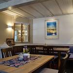 Frühstücks und Aufenthaltsraum mit Weißer Decke und beiger Wand, Holztische mit Holzstühlen und einem blauen Gemälde in der Panorama Pension Ahrklause Dernau.