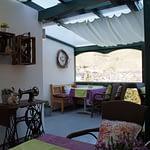Terasse mit einer alten Nähmaschiene, Rattanstühle einem Tisch mit Lila Tischdecke und grünem Tischläufer mit Aussicht auf Dernau und die Weinberge, der Panorama Pension Ahrklause Dernau.