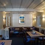 Frühstücks und Aufenthaltsraum mit Weißer Decke und beiger Wand, Holztische mit Holzstühlen einer weißen Gaderobe und einem blauen Gemälde in der Panorama Pension Ahrklause Dernau.